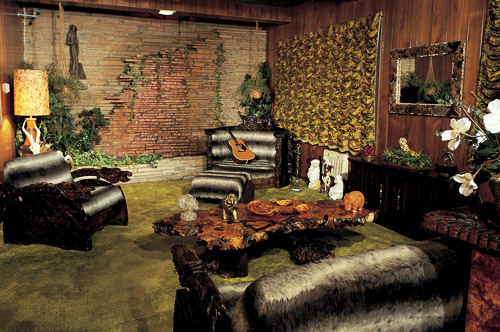 The jungle room. (Sorry for the terrible photos!) The red stone wall had a waterfall coming down it, and he had lots of polished wood furniture imported. Elvis had green shag carpets installed throughout, and a plethora of stuffed or sculpted animals.